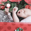 A christmas toddler in a gift in front of a fir — Stock Photo #65394193