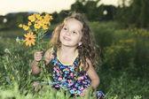 Маленькая девочка в закат с цветком — Стоковое фото