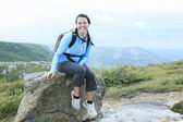 Female hiker with backpack walking and smiling on a country trai — Stock Photo