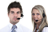 Young employee working with a headset and accompanied by his team — Stock Photo