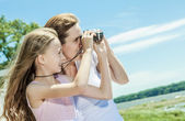 Young mother and her young daughter fun time together outdoors. — Stock Photo