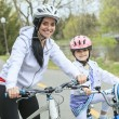 Beautiful and happy young on bicycle with her daughter. — Stock Photo #76730699