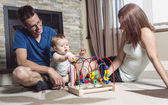 Parents baby sitting on floor play with toy — Stock Photo