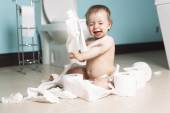 Toddler ripping up toilet paper in bathroom — Stock Photo