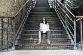 Young pretty stylish woman sitting on stairs — Stock Photo
