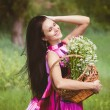 Beautiful girl with flowers. Brunette with a basket of flowers. — Stock Photo #60130655