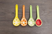 Spoons of different colors on wood background — Stock Photo
