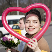 Face of a young adorable woman framed in the heart-shaped balloo — Stock Photo