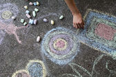 Woman paints with colored chalk on asphalt - Stock Image — Stock Photo