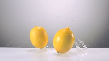 Whole lemons falling on water — Stock Video