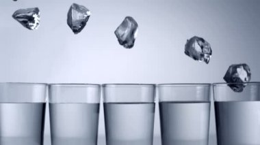 Ice cubes falling into glasses — Stock Video