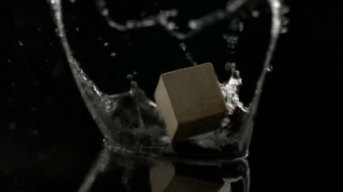 Wooden block falling and spinning on water — Stockvideo