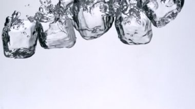 Ice cubes falling in water — Stock Video