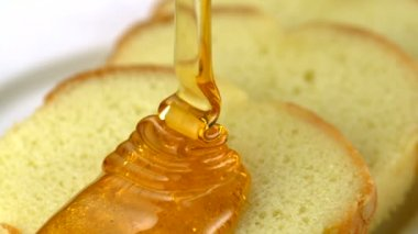 Pouring honey on a piece of bread — Vídeo de stock