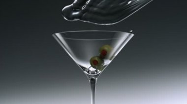 Water splash and olives in martini glass — Stock Video
