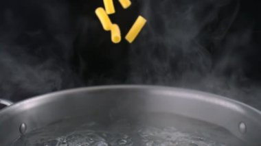 Throwing tortiglioni pasta into boiled water — 图库视频影像