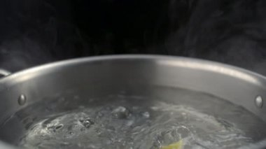 Throwing farfalle pasta into boiled water in pot — Stok video