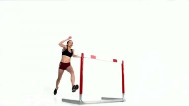 Female athlete jumping over hurdle — Stock Video