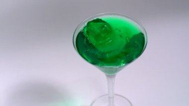 Green jelly falling in drink — Stock Video