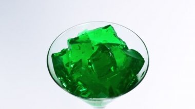 Green jelly falling in martini glass — Stock Video