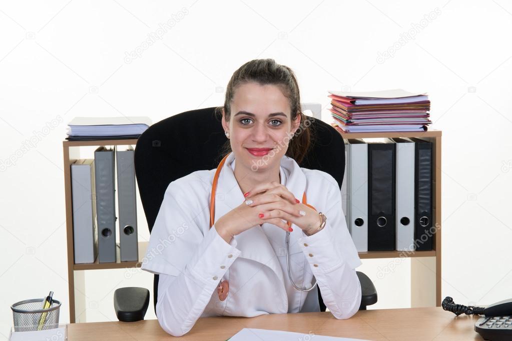 Jeune m decin souriant assis au bureau sur une chaise for Assis sur une chaise