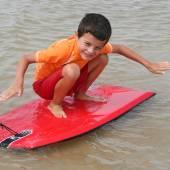 Surf kid in water beach — Stock Photo