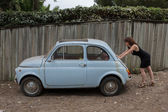 Woman is pushing a small blue car break down — Stock Photo