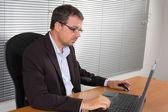 Zdůraznil podnikatel sedí za stolem držel za hlavu a obav — Stock fotografie
