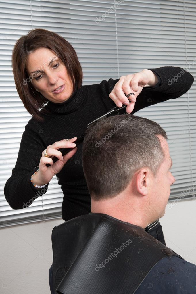 Homme à la situation de salon de cheveux avec le coiffeur féminin ...