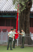 Law enforcement officers raising the Chinese flag — Stock Photo