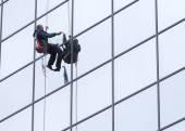 Sanitation worker cleaning glass facade hotel — Zdjęcie stockowe