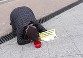 Beggar lying on the ground — Stock Photo