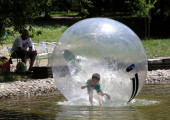 Child in water baloon sphere — Stock Photo