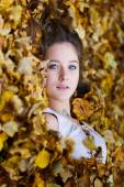 Beautiful girl in a yellow leaves — Stock Photo