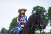 Beautiful young girl riding a horse in countryside — Stock Photo