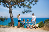 Family with two kids on the seacoast — Stock Photo