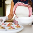 Young woman puts candied fruits on the cakes — Stock Photo #83022246