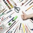 Set of pens, pencils and paints with hand on a white background — Stock Photo #77228236