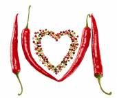Red hot pepper in pods and colorful mixture of peppercorns. Concept of love. — Stock Photo