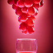 Ripe red grapes with glass of wine. On red background — Stock Photo #57916389