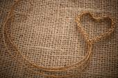 Valentines Day. Handmade Heart made of twine on sackcloth — Stock Photo