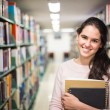 In the library - pretty female student with books working in a h — Stock Photo #60215139