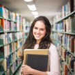 In the library - pretty female student with books working in a h — Stock Photo #60215179