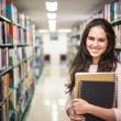 In the library - pretty female student with books working in a h — Stock Photo #60215217