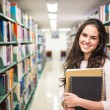 In the library - pretty female student with books working in a h — Stock Photo #60215243