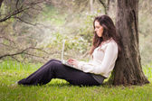 Young beautiful woman using a laptop computer at the park — Stock Photo