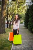 Shopping young girl holding shopping bags looking to the camera — Stockfoto