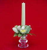Candle holder with green pillar candle against red background — Photo