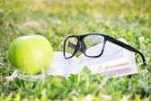 Glasses, book and apple on a green grass — Stock Photo