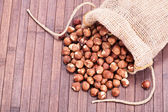 Spilled hazelnuts on wooden background — Stock Photo